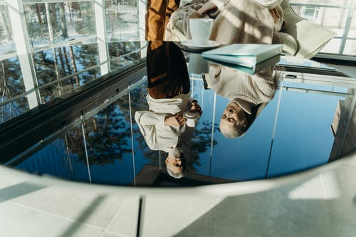 Reflections of Elderly Man and Woman on Glass Surface