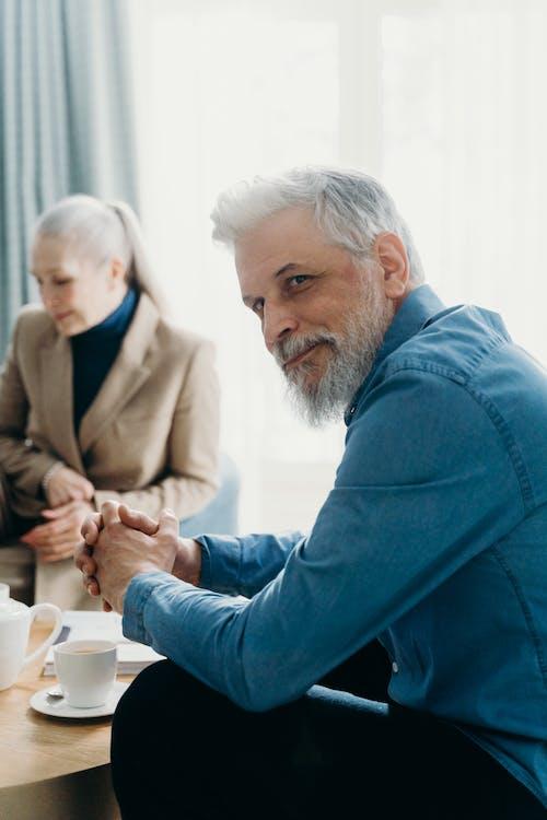 Elderly Man in Blue Denim Jacket Sitting with Hands Clasps Together