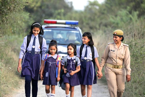 Group of Young Girls Walking with a Police Woman