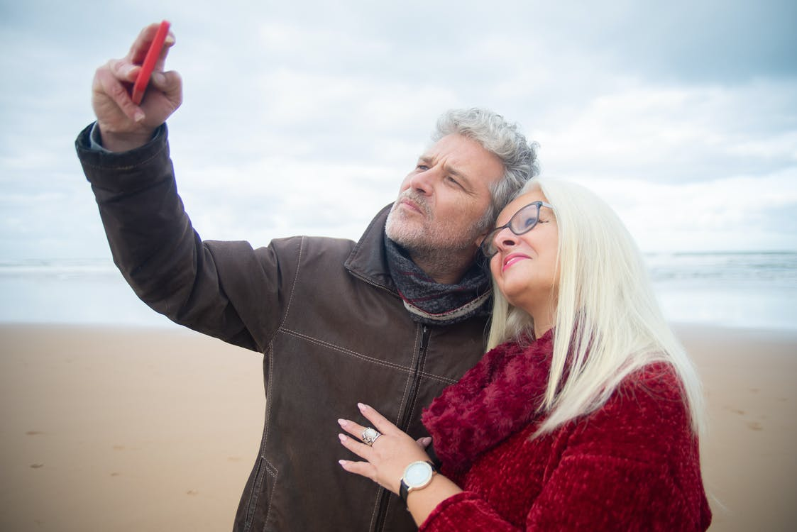 Man in Gray Zip Up Jacket Holding Woman in Red Fur Coat