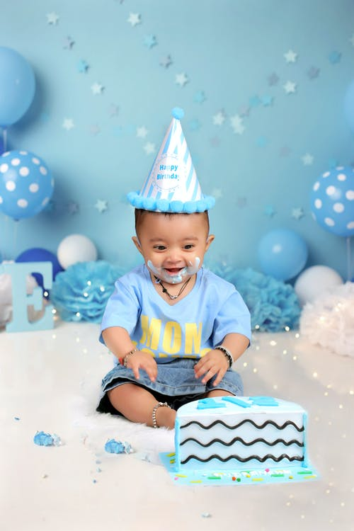 Adorable happy little boy admiring colorful birthday cake among blue balloons in decorated studio