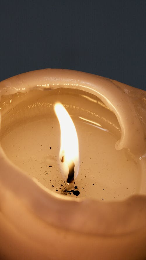 White Candle on Clear Glass Container