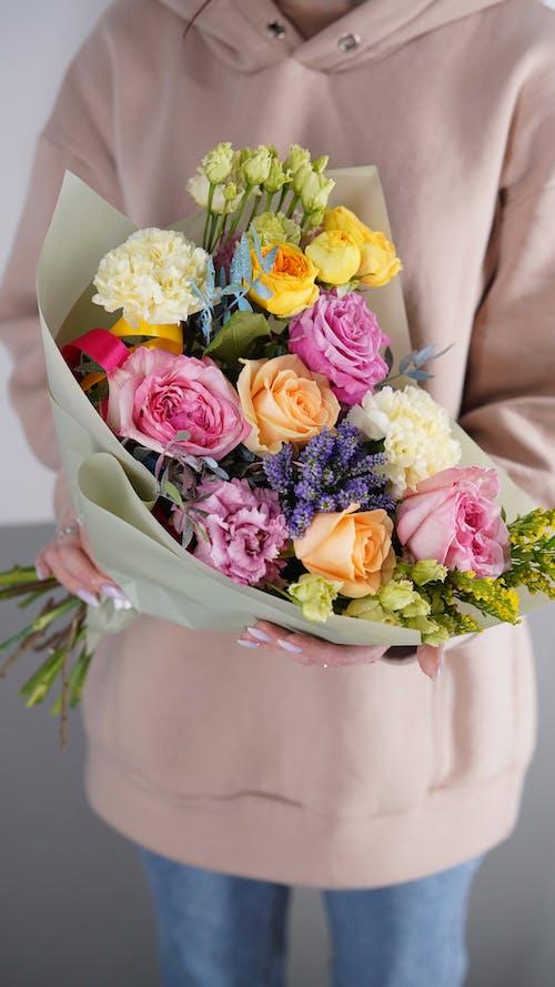 Crop unrecognizable woman holding vibrant fragrant bouquet