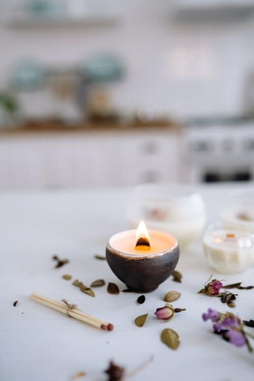 Lighted Candle on Black Ceramic Pot