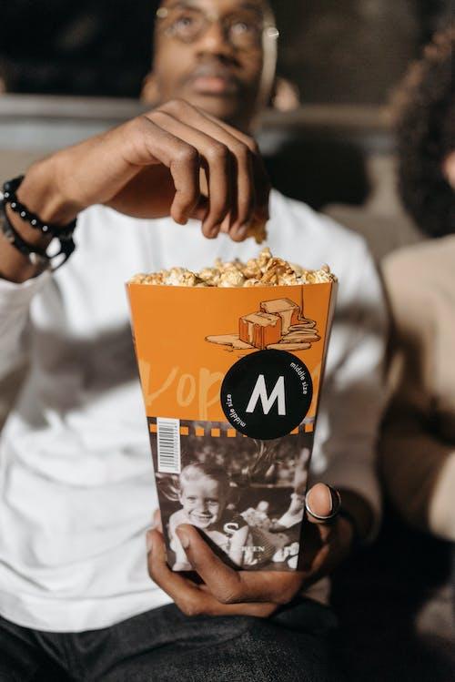 Photo of a Man Holding a Bucket of Caramel Popcorn
