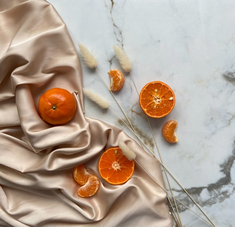 Top view of fresh ripe slices of tangerine and oranges placed on crumpled fabric on marble surface with dried branches