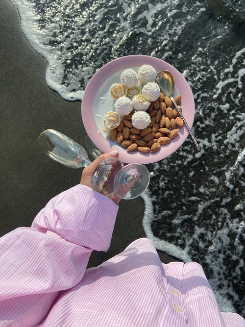 Top view of anonymous female with wineglasses and plate with nuts and candies in hand standing on wet beach near waving sea