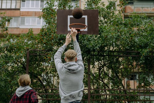 Woman in Gray Sweater Holding Basketball