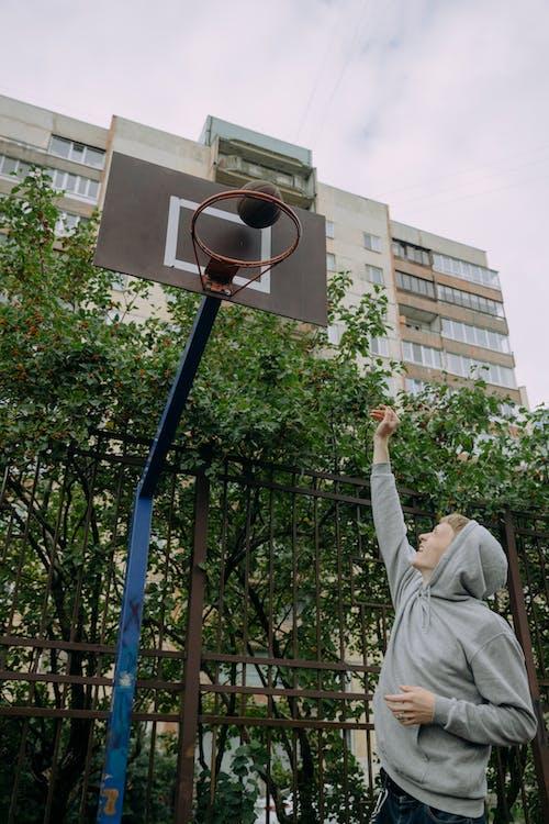 Man in White Long Sleeve Shirt Holding Basketball Hoop