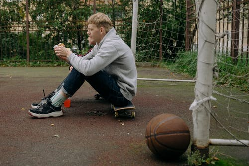 Boy in Gray Hoodie Playing Basketball