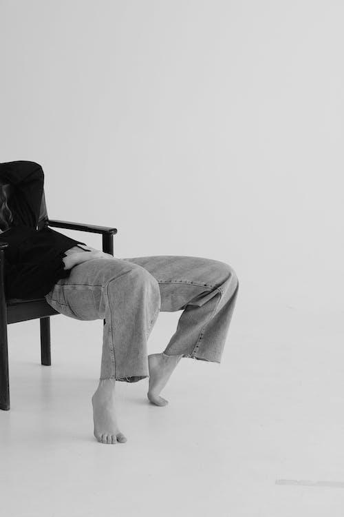 Crop anonymous woman resting in armchair in studio