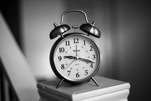 Grayscale Photo of Twin Bell Alarm Clock