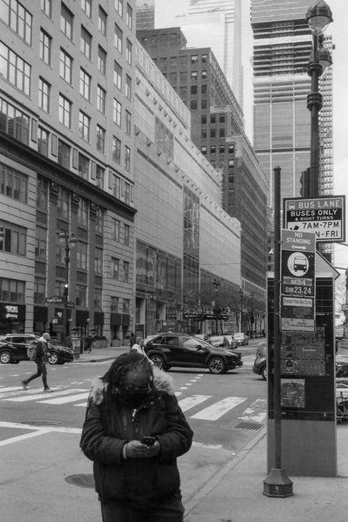 Grayscale Photo of Woman in Black Jacket Standing on Pedestrian Lane