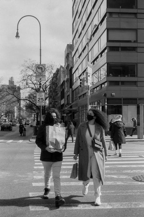 Grayscale Photo of Woman in Coat Walking on Sidewalk