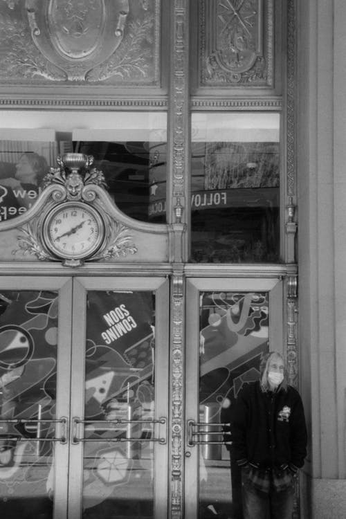 Grayscale Photo of Man in Black Jacket Standing in Front of Store
