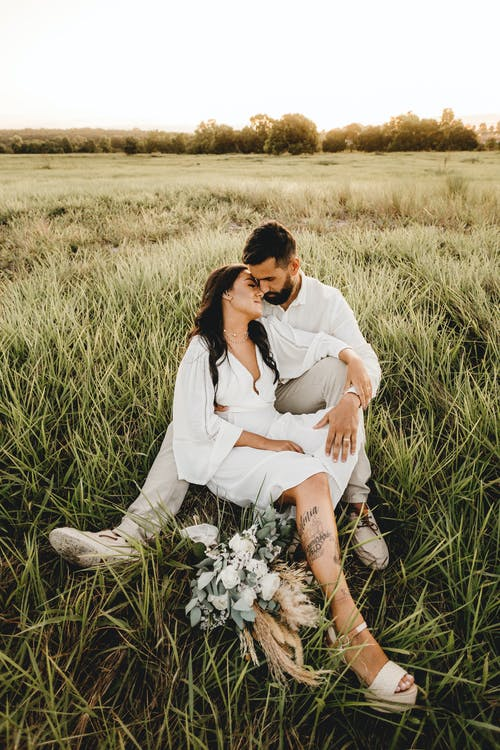Ethnic groom with bride embracing on meadow on wedding day