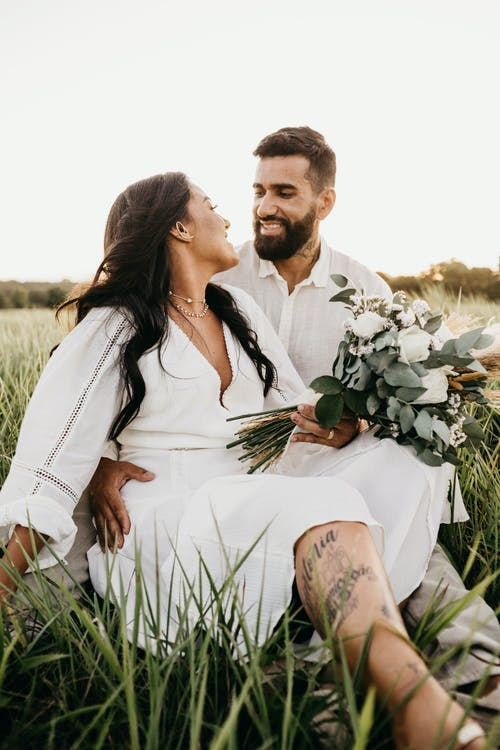 Smiling ethnic newlywed couple embracing in countryside field