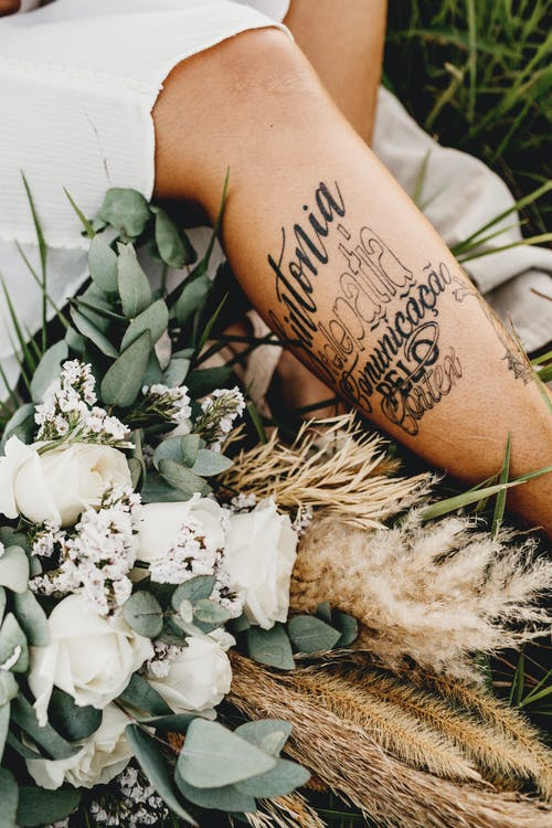 Woman with tattoos siting on grass with bunch of flowers