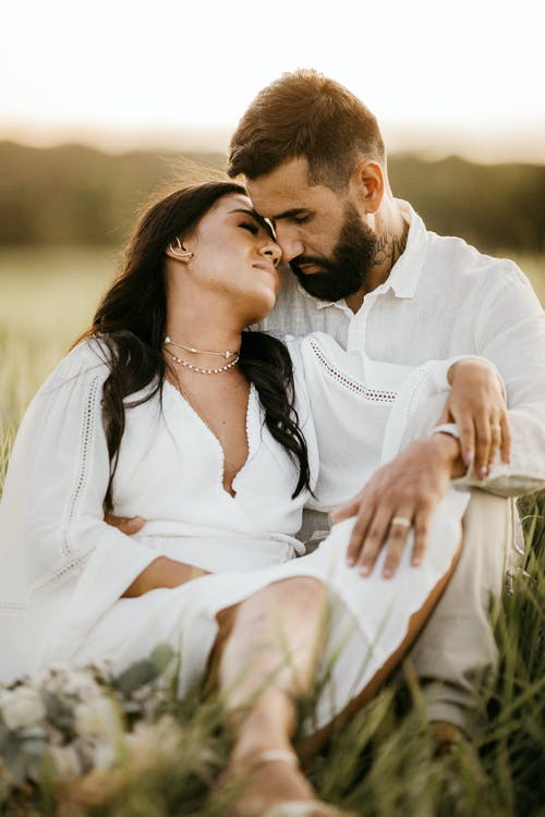 Loving gentle couple caressing while sitting close in meadow