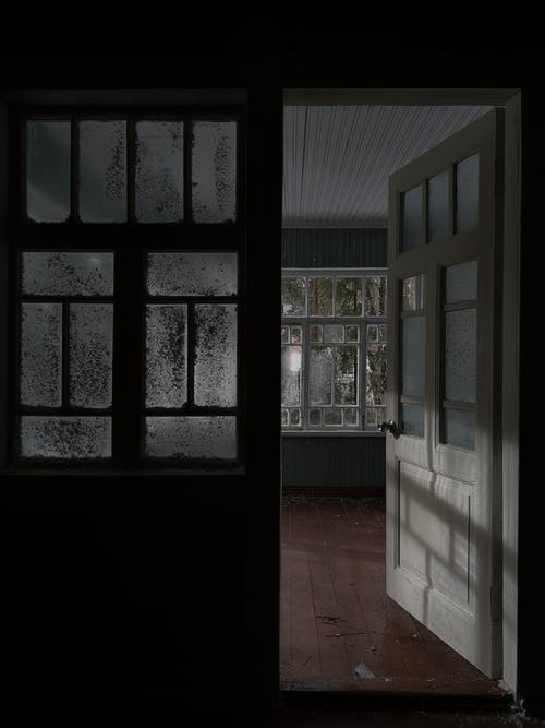 Opened door leading to empty light room with large windows placed in house in daytime