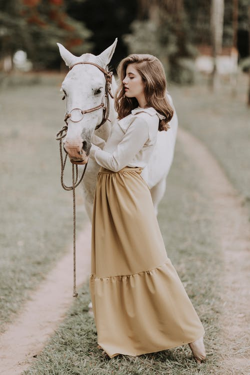 Side view of young romantic barefooted female with long wavy hair in elegant outfit stroking purebred light gray horse in countryside