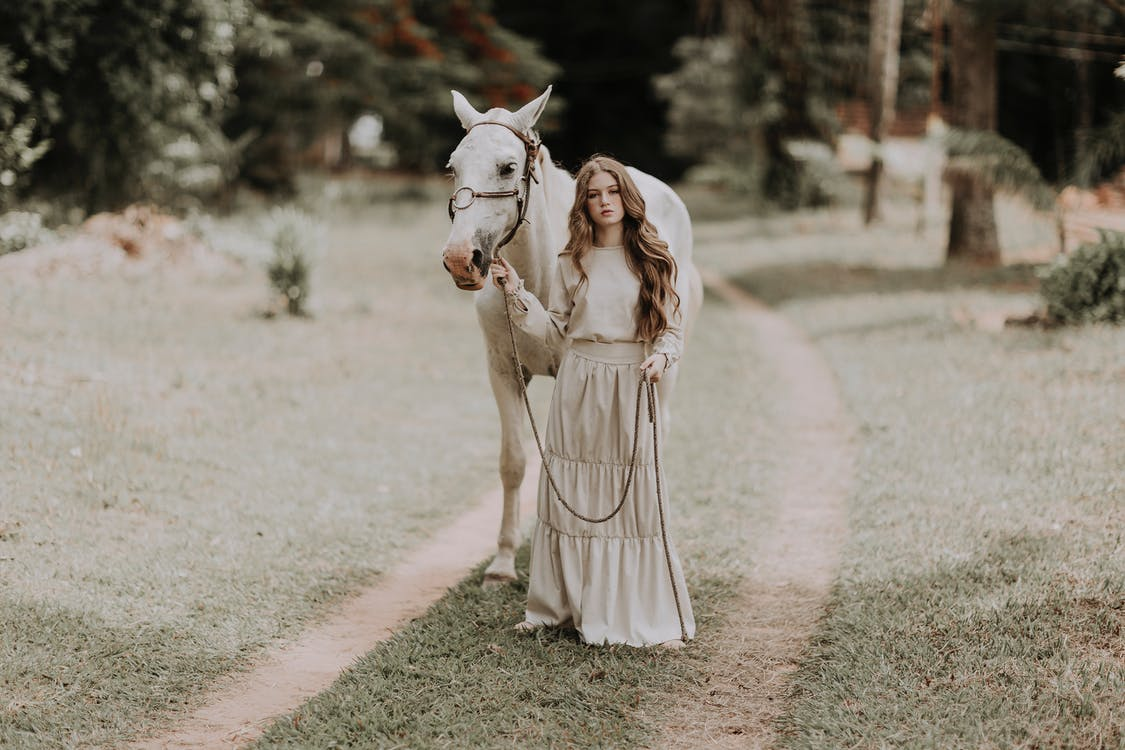 Full body of stylish young female owner with long wavy hair in elegant maxi skirt standing on grassy path near obedient purebred horse during holidays in countryside
