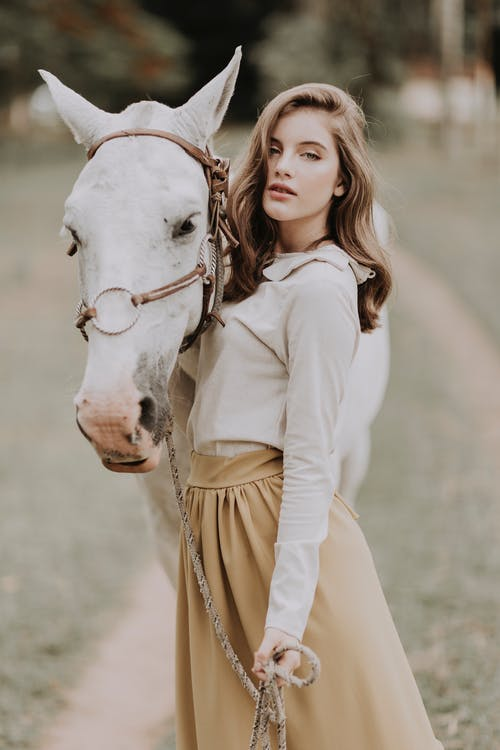 Gorgeous young woman embracing calm horse in nature