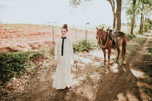 Stylish young woman walking in countryside with obedient chestnut horse in sunlight