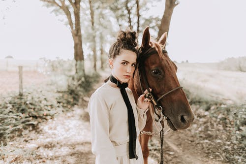 Elegant young woman standing on rural footpath with obedient horse