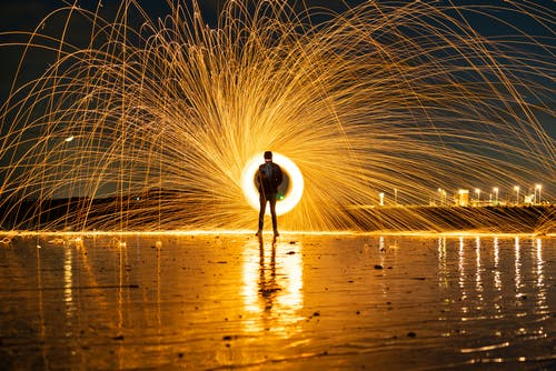 Person Standing on Dock With Fireworks Display during Night Time