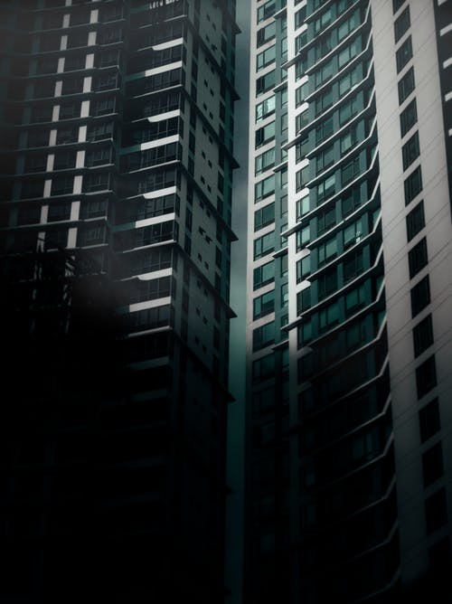 Exterior of contemporary high rise apartment buildings with windows located on street with dark shadow in modern district of city