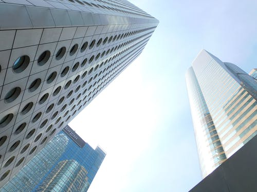 From below of tall tower with round windows located in Hong Kong city near various skyscrapers with glass mirrored facades against cloudless blue sky
