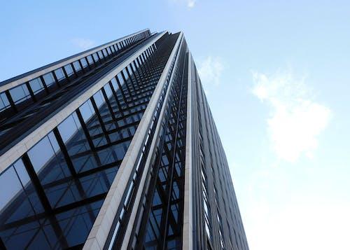 Glass facade of contemporary skyscraper in city on sunny day