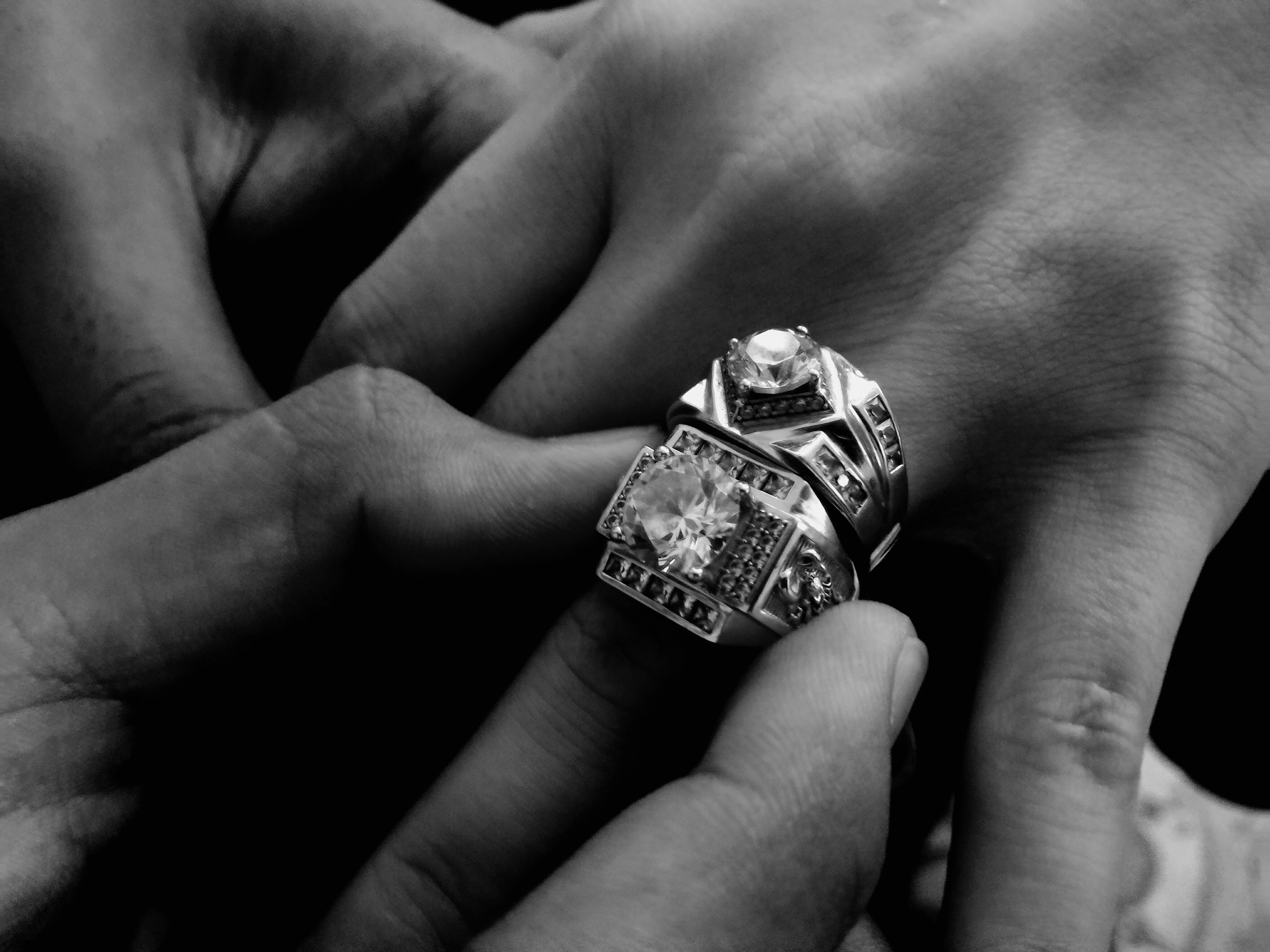 Grayscale Photo of Person Wearing Two Diamond-encrusted Rings