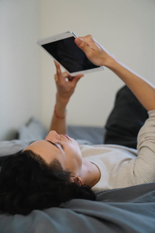 Young man relaxing on bed and watching video on tablet with black screen on weekend day at home