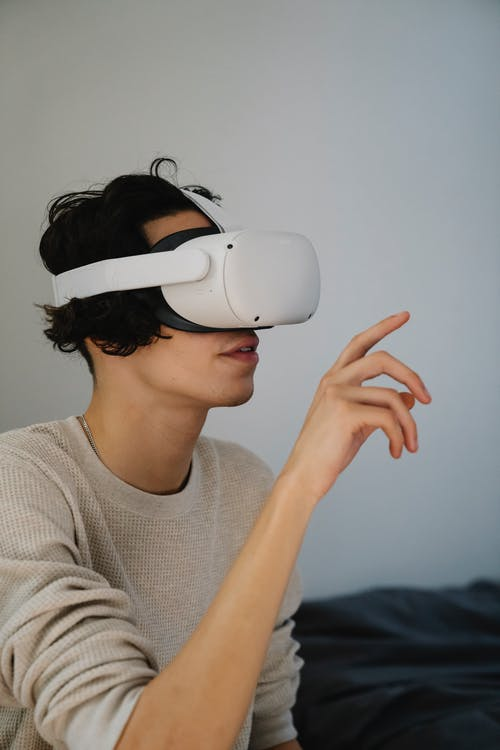 Amazed young man experiencing virtual reality in contemporary headset