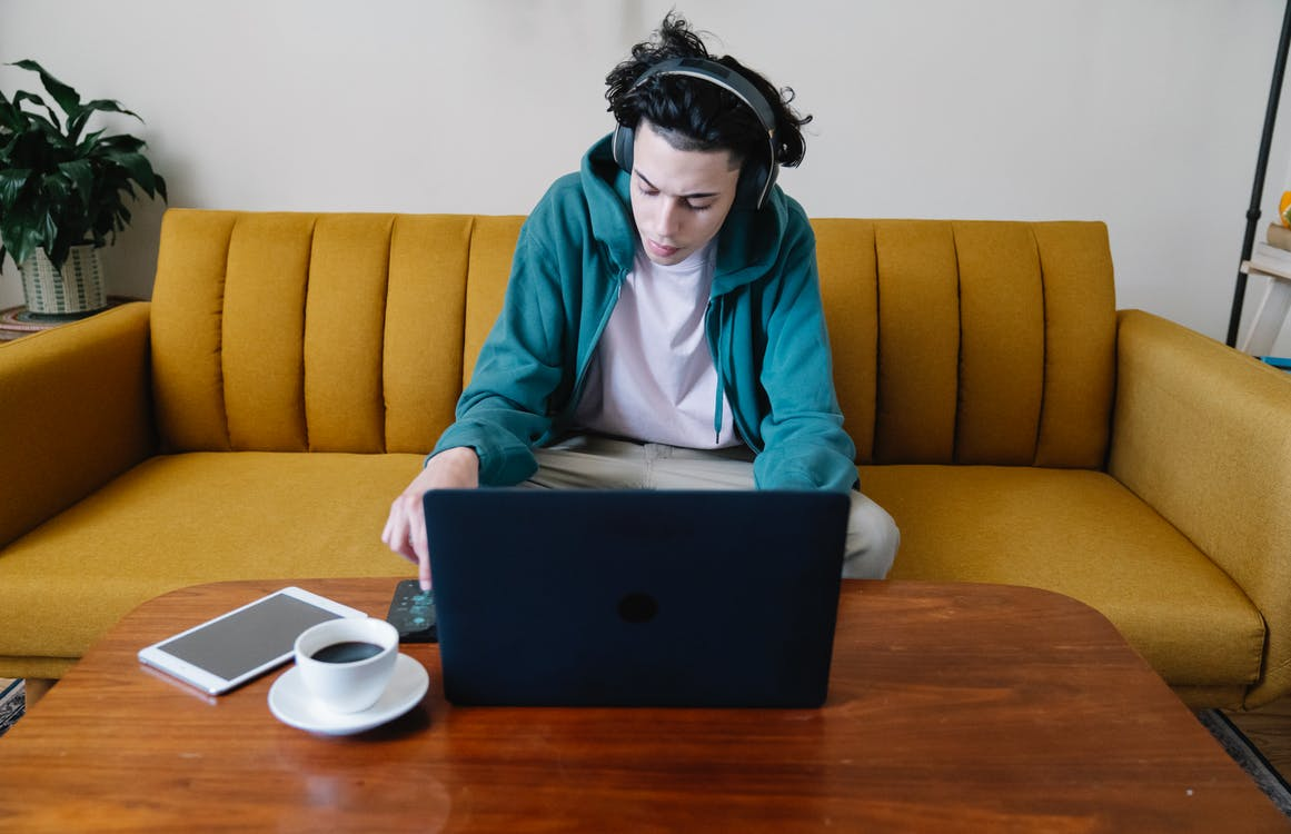 High angle of busy young male in headphones sitting on sofa and using cellphone at table with netbook coffee and tablet