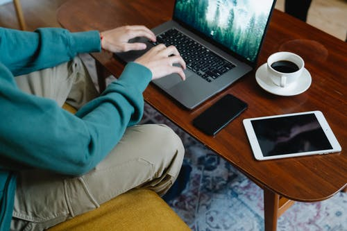 High angle of crop anonymous male remote worker working on netbook at table with cup of coffee placed near cellphone and tablet