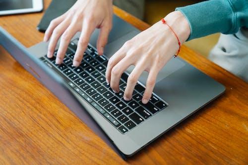Man typing on keyboard while working on laptop