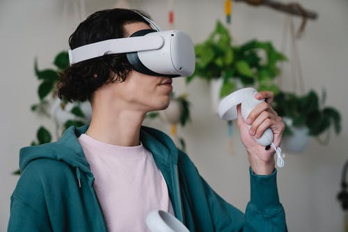Young man playing videogame in VR headset with controller
