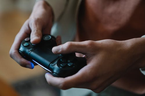 Crop gamer with joystick playing video game at home