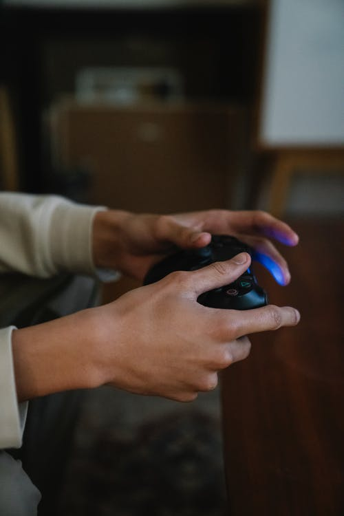 Crop gamer with console controller playing video game in room