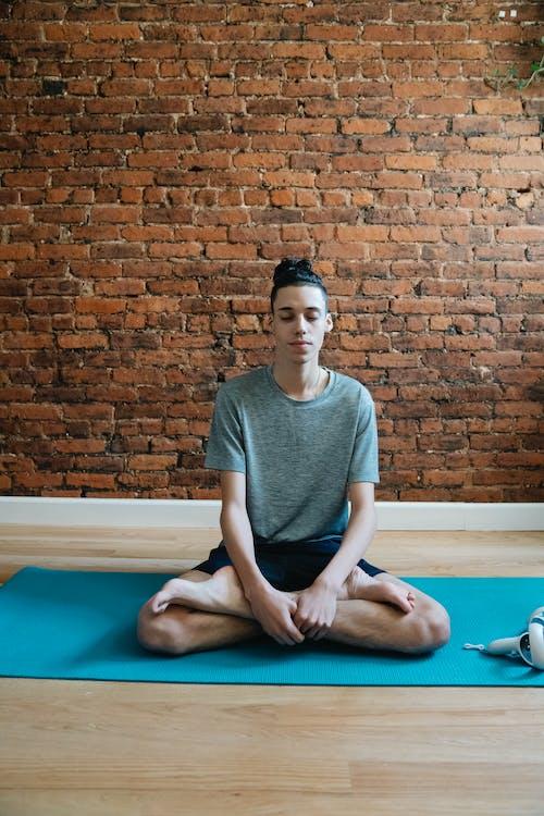 Teen boy doing Padmasana on mat
