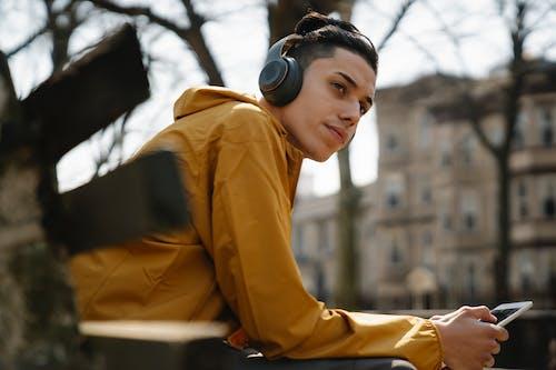 Teen boy with headphones using mobile phone