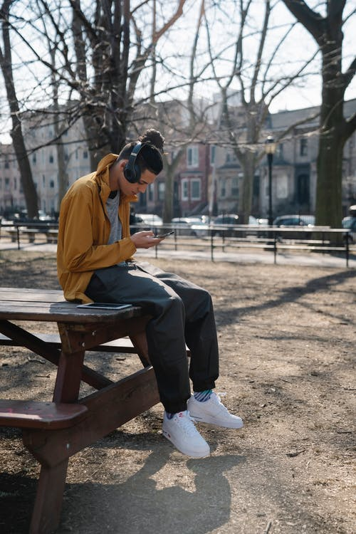 Focused male teenager with headphones using smartphone and listening to music while sitting in park