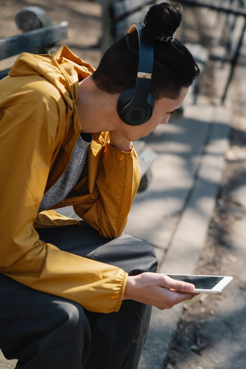 Side view of young man siting on bench in sunny park and using tablet while listening to music in headphones