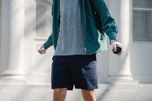 Crop anonymous male in casual outfit holding modern white controllers while waling near white wall on street