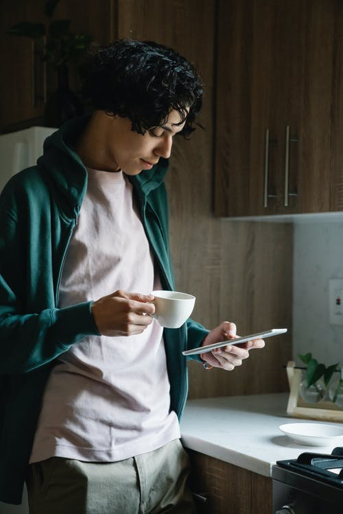Attentive ethnic male with cup of hot drink text messaging on cellphone at home in daytime