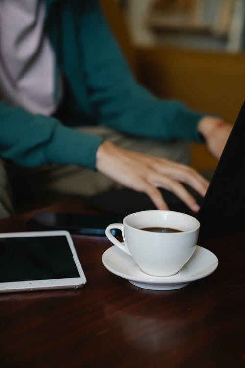 Crop freelancer typing on laptop against coffee at home