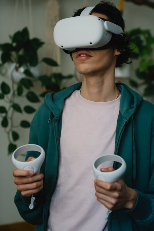 Male in virtual reality goggles with controllers playing video game while having free time in house